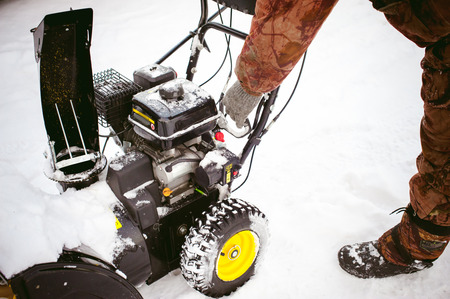 man starts the engine snow blower Standard-Bild