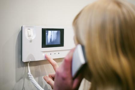 귀에 전화기를 잡고 금발의 여자는 인터콤 전화에 응답