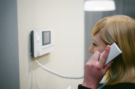 blonde woman answers the intercom call while holding the phone to your ear Standard-Bild