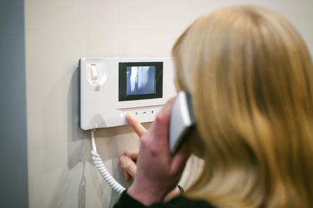 blonde woman answers the intercom call while holding the phone to your ear Stock Photo
