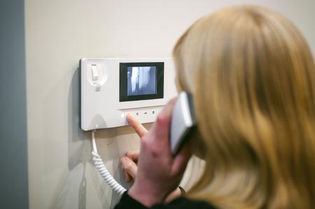 donna bionda risponde alla chiamata interna mentre tiene il telefono all'orecchio Archivio Fotografico