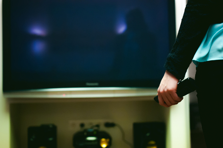 switching: girl in a home environment, holding a TV remote, switching channels Stock Photo