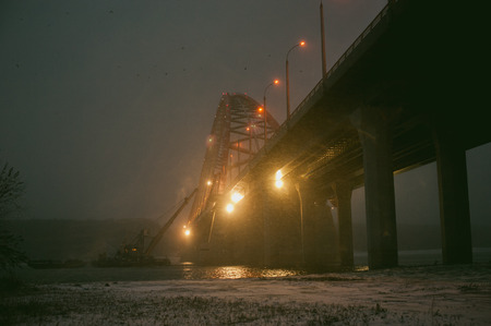 dredging: river dredge produces sand from the bottom of the bridge, after dark Stock Photo