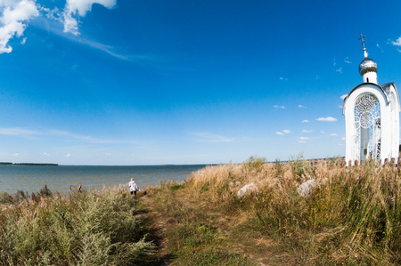 Orthodox chapel white with a transparent façade on the background of the panorama of the sea and blue sky in a field, enclosed by a wooden fence, summer day, an old woman parishioner