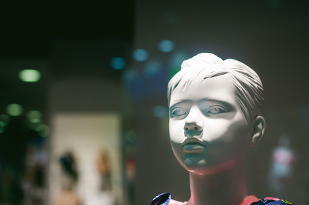 dummy on a shop window. Child face in the background of the store Stock Photo