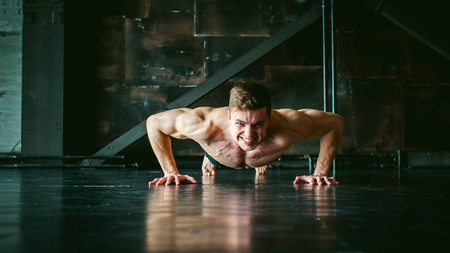 bare skinned: Young sexy male bodybuilder athlete with a bare torso. portrait of a studio of a light-skinned strong man engaged in push-ups, on the floor, straining powerful hands Stock Photo
