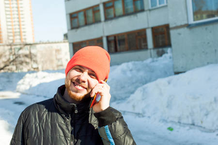 man Emotionally communicates by telephone. guy with beard, dressed in an autumn sports casual jacket and bright orange hat, Speaks by cell phone in stylish case, walking outdoors on sunny winter day