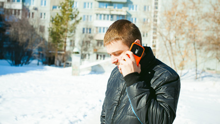 Telephone calls men. The guy is talking on cell phone in street in winter, dressed in warm clothes, holds in his hand phone at ear, in bright orange sheath case Stock Photo