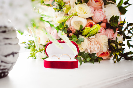Photo image of a red velvet box with wedding rings of the bride and groom, on a white table, with a bridal bouquet of bridal flowers