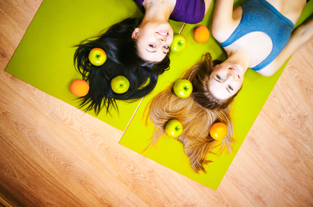 Two young athletic physique women in gym Lie on the floor on yoga mats. Fitness girl with fruits, lifestyle in losing weight and diets, proper nutrition, exercise