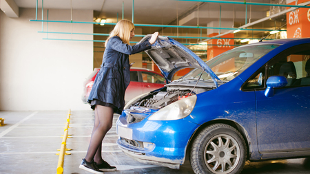 woman near cars hood. young blonde in covered parking of shopping center, stands near car with raised engine compartment hood, solves problem with malfunction by phone call to service Stock Photo