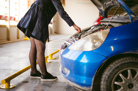 woman near cars hood. young blonde in covered parking of shopping center, stands near car with raised engine compartment hood, checks engine oil level in engine, inspects feeler gauge