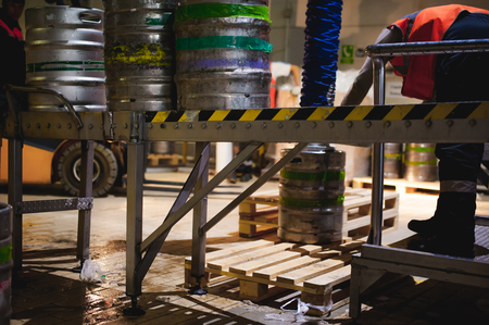 Process of transfer of aluminum kegs from filling line to pallet, employee of production line at brewery, work on special production equipment. human labor in manufacturing Stock Photo