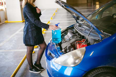 woman near cars hood. young blonde in covered parking of shopping center, stands near car with raised engine compartment hood, pours liquid to wash glass in tank, holding cone in hands Stock Photo