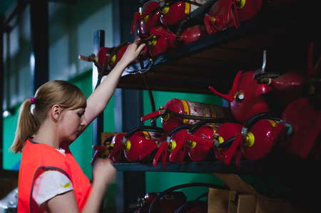 Checking fire extinguishers in the warehouse. Woman Engineer shall record and verify the presence of fire extinguishers Stock Photo