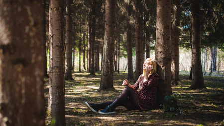 lady on phone: Walk girl coniferous forest park. blonde woman dressed summer dress, black pantyhose and sneakers with white sole, resting nature enjoying warm sunny day. Sits under tree alone, Speaks cell phone