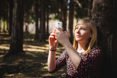 lady on phone: blonde woman dressed summer dress, black pantyhose and sneakers with white sole, resting nature enjoying warm sunny day. Sits under tree alone, holding in hand cell phone, Emotion online communication