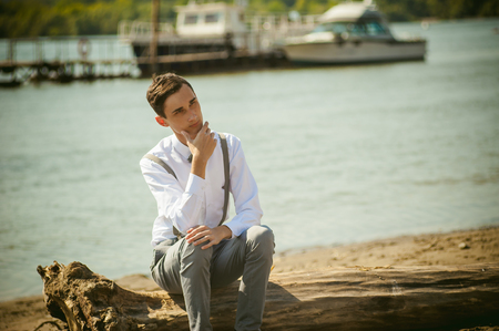 stylishly: young skinny man, elegantly stylishly dressed in white shirt, gray trousers with suspenders and bow tie. Portrait young guy on pier on background of river and boats