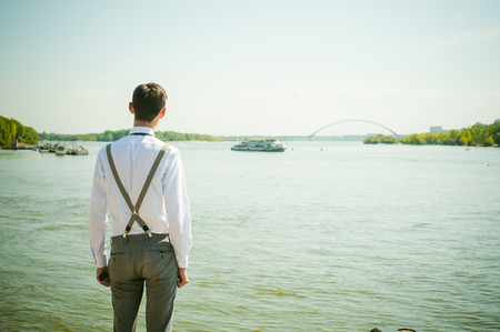 young skinny man, elegantly stylishly dressed in white shirt, gray trousers with suspenders and bow tie. Looking away, at the river water bridge and ship