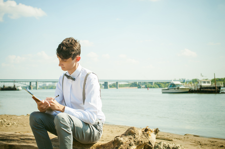 stylishly: young skinny man, elegantly stylishly dressed in white shirt, gray trousers with suspenders and bow tie. young guy on pier on background of river and boats, takes notes of pen on sheet in notebook Stock Photo