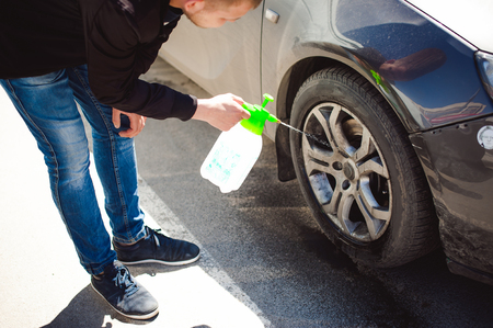 alloy: young bearded man washes his cars wheel rims, spraying water from spray, in street parking Stock Photo