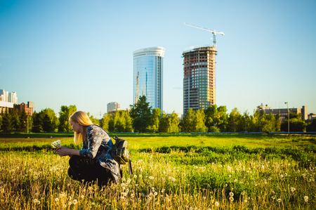 Young blonde girl in dress with shoulder bag, walking on dandelion field, against background of urban architecture, breathing relaxing in cityscape Stock Photo