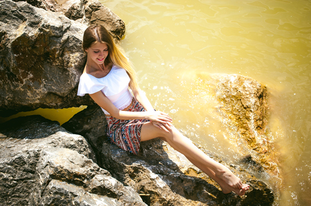 Portrait of slender young woman on stones near the sea. Beautiful girl is resting on coast, enjoying outdoor recreation