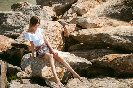 Portrait of slender young woman on stones near the sea. Beautiful girl is resting on coast, enjoying outdoor recreation. Graceful long thin tender arms and legs Imagens