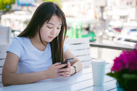 Cute asian young woman in summer cafe outdoors. girl In white T-shirt, with long hair in simple light cozy interior of restaurant Urban style, Communicates on a cell phone holding it in his hands Stock Photo