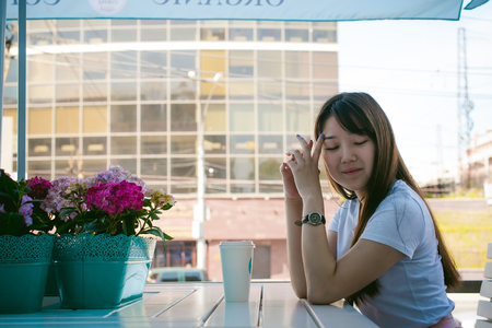 Cute asian young woman in summer cafe outdoors. girl In white T-shirt, with long hair in simple light cozy interior of restaurant Urban style, drinking coffee drink, sitting at table with flowers