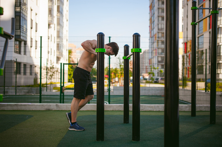 Handsome sexy male bodybuilder athlete man doing crossfit workout in athletic facilities on sunny morning outdoors. Healthy lifestyle concept. Rest after exercise.