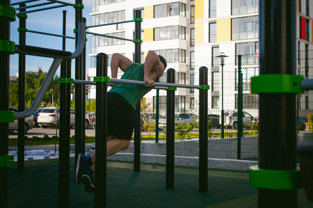 Handsome sexy male bodybuilder athlete man doing crossfit workout in athletic facilities on sunny morning outdoors. Healthy lifestyle concept. Physical preparation of the body