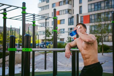 Apuesto hombre de atleta sexy bodybuilder haciendo crossfit entrenamiento en instalaciones atléticas en la mañana soleada al aire libre. Concepto de estilo de vida saludable. Descansar después del ejercicio, beber agua de una botella