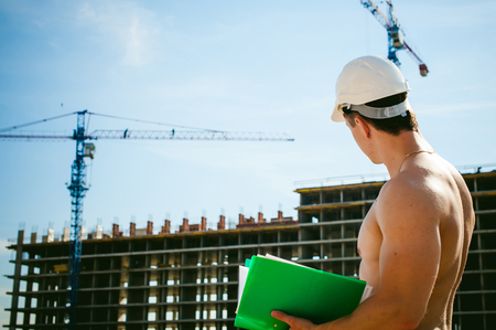 Jonge sexy mannelijke bodybuilderatleet met een naakt torso. De ingenieurbouwer van de manager in witte beschermende helm bevindt zich op achtergrond van bouw van bouw en bouwkranen met documentatie Stockfoto