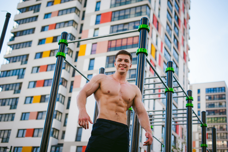 Handsome sexy male bodybuilder athlete man doing crossfit workout in athletic facilities on sunny morning outdoors. Healthy lifestyle concept. Physical preparation of body. Model poses showing muscles