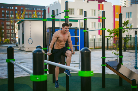Handsome sexy male bodybuilder athlete man doing crossfit workout in athletic facilities on sunny morning outdoors. Healthy lifestyle concept. Stock Photo