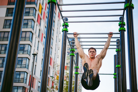 Handsome sexy male bodybuilder athlete man doing crossfit workout in athletic facilities on sunny morning outdoors. Healthy lifestyle concept. Physical preparation of body. pull-up on horizontal bar