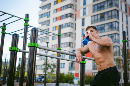 Handsome sexy male bodybuilder athlete man doing crossfit workout in athletic facilities on sunny morning outdoors. Healthy lifestyle concept. Rest after exercise, drinking water from a bottle