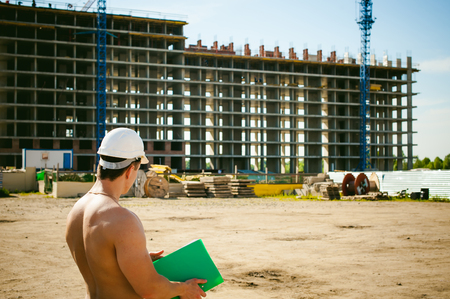 Young sexy male bodybuilder athlete with a bare torso. Manager engineer builder in white protective helmet stands on background of construction of building and construction cranes with documentation Stock Photo
