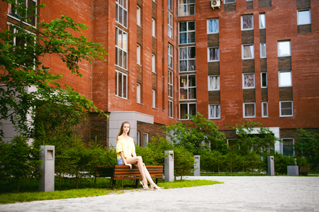 Portrait of a young pretty woman in blue denim  jeans shorts sitting on a bench in courtyard of a residential complex, against a background of green plants and houses, on a warm, sunny summer day.