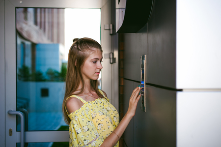 woman dials an apartment code on an electronic doorphone panel