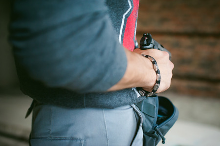 man pulls a gun out of his bag, holding it in his hand
