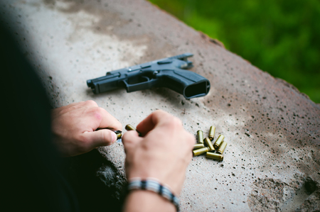 Man charges clip of pistol with bullets. Photo hands of paramilitary, reloading weapons. Preparation for shooting