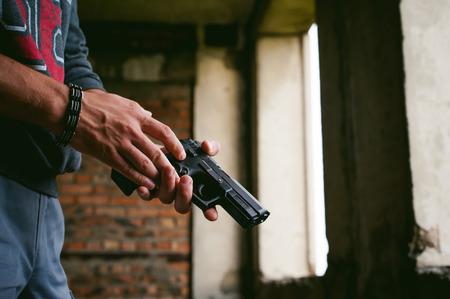 Gevaarlijke atletische mens die een kanon in zijn hand, close-up houdt Stockfoto