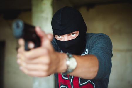 Athletic man in a balaclava, holds a pistol in his hand, is threatened with shooting, aiming