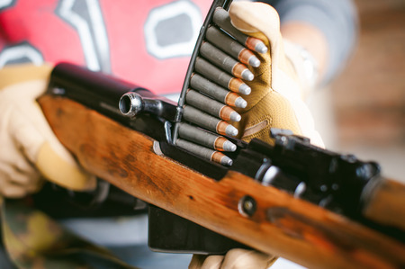 rifle carbine is weapon in hands. closeup tactical gloves  weapons, reloading ammunition. Soldier on a position performing a combat mission