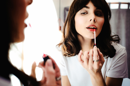 Portrait of a beautiful woman, dyes her lips lipstick pink, looking in the mirror
