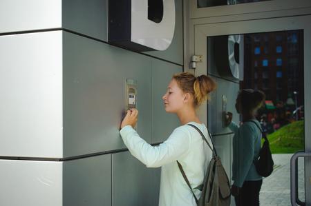 young blond teenager schoolgirl dials the code for a call over the intercom Foto de archivo