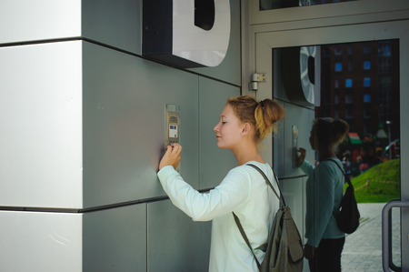 young blond teenager schoolgirl dials the code for a call over the intercom Standard-Bild