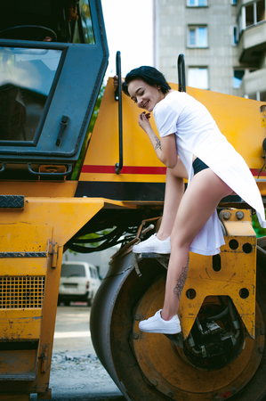young woman with bare feet dressed in white sneakers and a long jersey, against a backdrop of urban landscapes and road machinery, asphalt paver. Street fashion.